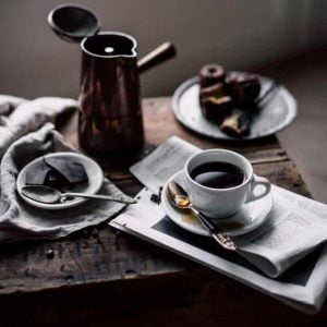 Black Tea served with chocolate on the side on a wooden table.